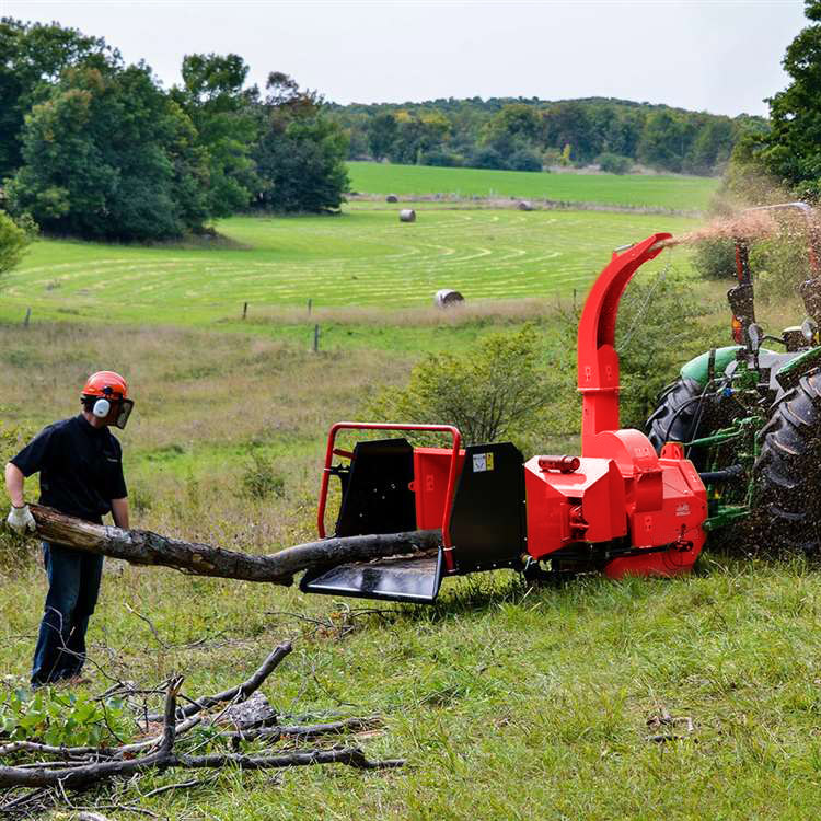 Photo of a man feeding a tree into a Grizzly woodchipper